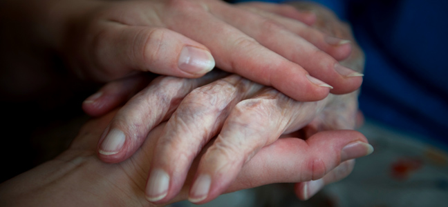 Holding-hands-comforting-an-elderly-lady